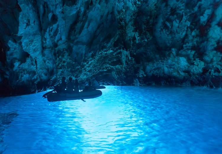 Tourists in inflatable boats inside the Blue cave, famous tourist attraction in Croatia.