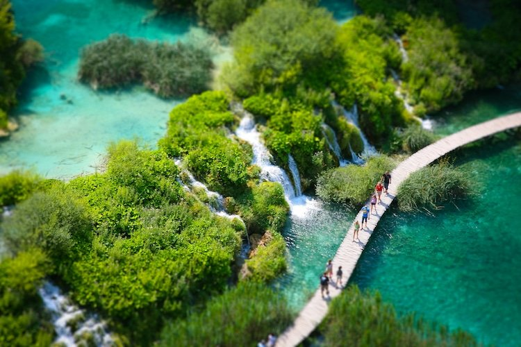 people walking in boardwalks near waterfall in Plitvice Lakes National Park Croatia