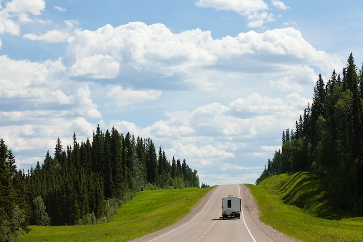 Recreational Vehicle RV on empty road of Alaska Highway, Alcan, in boreal forest taiga landscape south of Fort Nelson, British Columbia, Canada