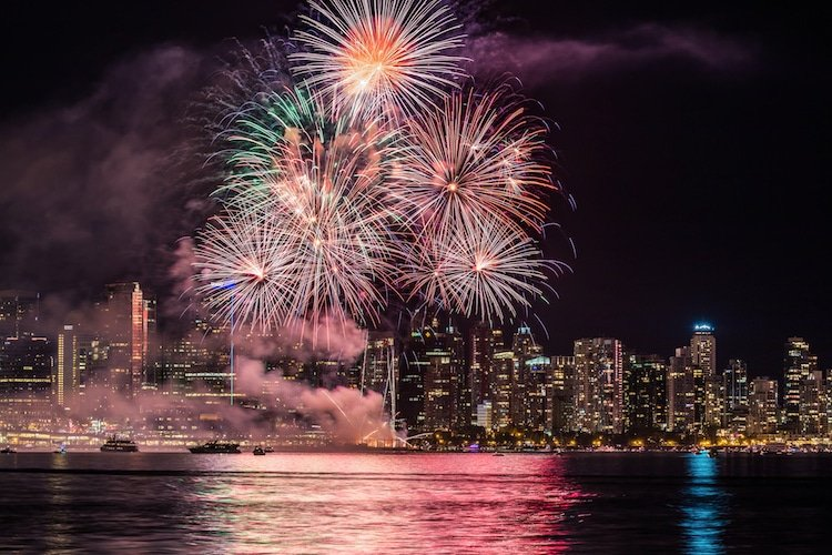 Fireworks light up the Vancouver Skyline above the water.