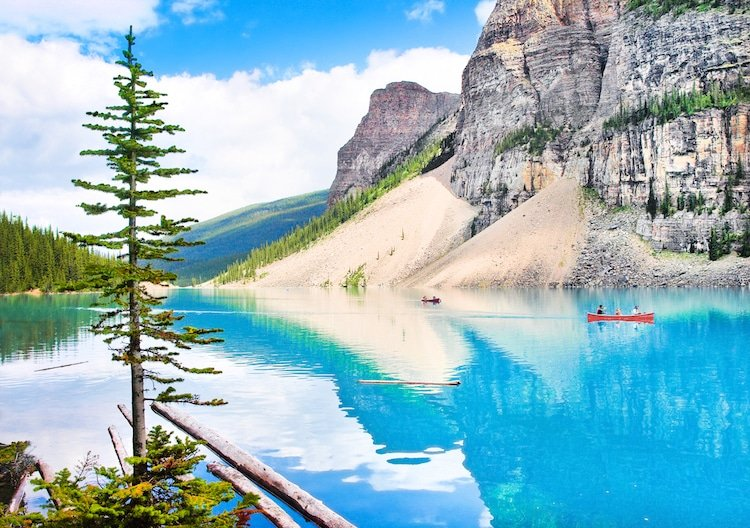 A red canoe floats in a glacial blue late among mountains in British Columbia, Canada