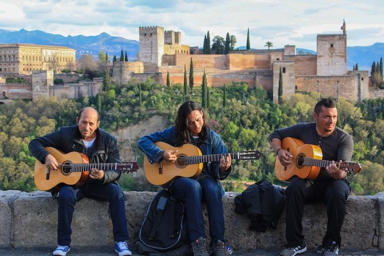 Three men play guitar in front of the Alhambra in Granada, Spain
