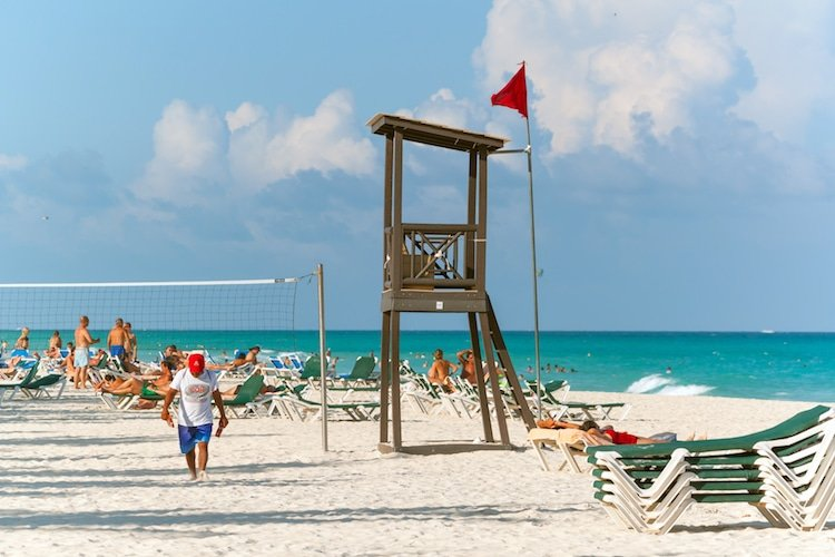 Calle 2 Beach in Playa del Carmen with a lifeguard's station, lounge chairs, and people playing beach volleyball.