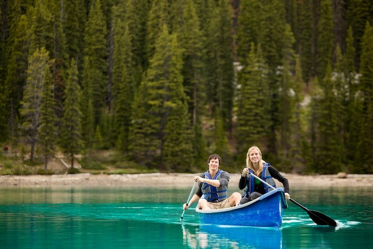 A portrait of two people in a canoe on a glacial lake in Banff National Park