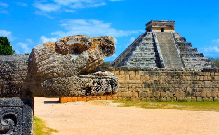 A head statue in the foreground and a pyramid in the background at Chichen Itza, Mexico