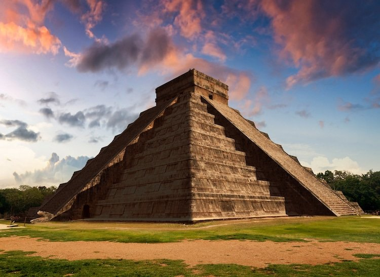 The sun setting behind the main pyramid at Chichen Itza, Mexico
