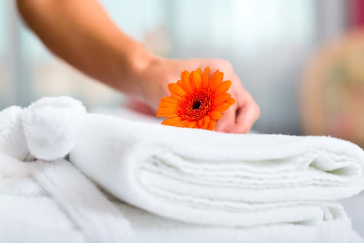 an orange flower on top of fluffy white towels