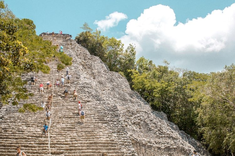 People climbing the big pyramid at Coba in Mexico, a popular excursion from Playa del Carmen