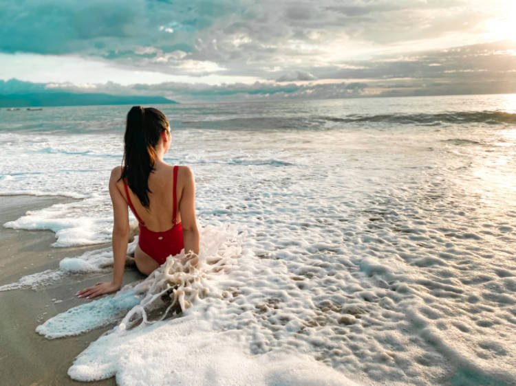 The author sitting on the sand above the sea on the Conchas Chinas Beach