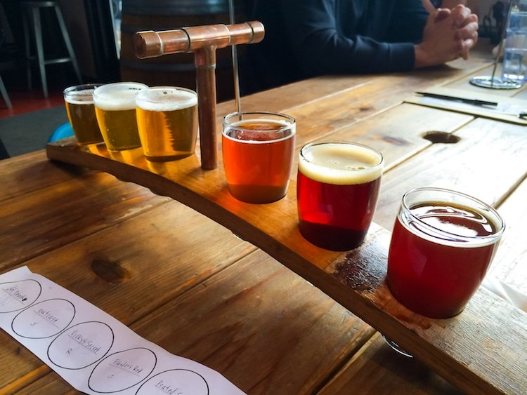 A flight of craft beer on a wooden table