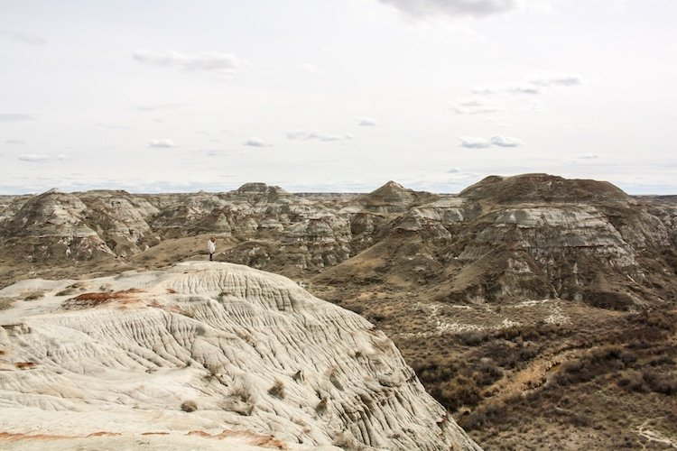 A woman stands atop carved sandstone rock in Dinosaur Provincial Park Alberta Canada