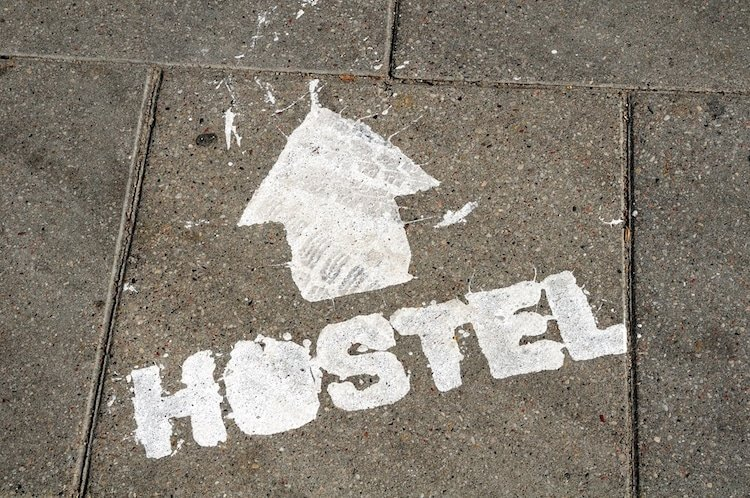 hostel sign on ground with arrow showing direction