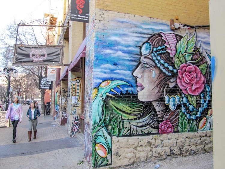 Two girls walk down the street in Winnipeg's Exchange District next to a mural.