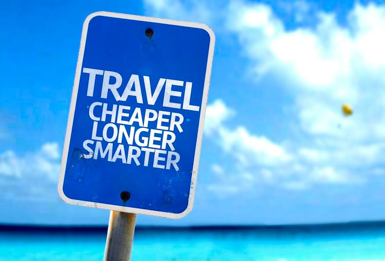 "Blue sign that says ""travel cheaper, longer, smarter"" with ocean in background"