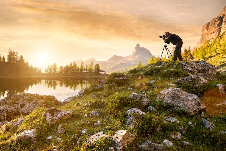 A photographer taking a photo of a beautiful lake at sunset