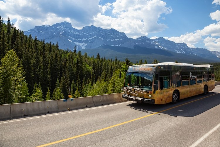 Lake Minnewanka, Banff, Alberta, Canada -  Public bus riding on the scenic road during a sunny summer day.
