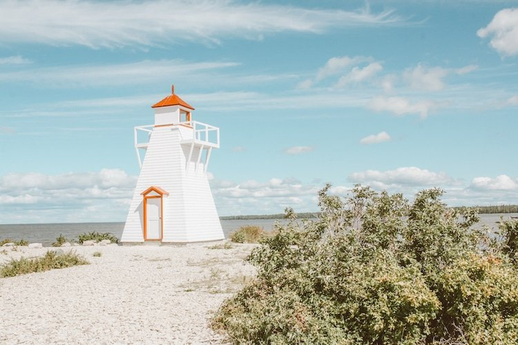A white and red lighthouse stands on a beach of Lake Winnipeg in Hecla, Manitoba