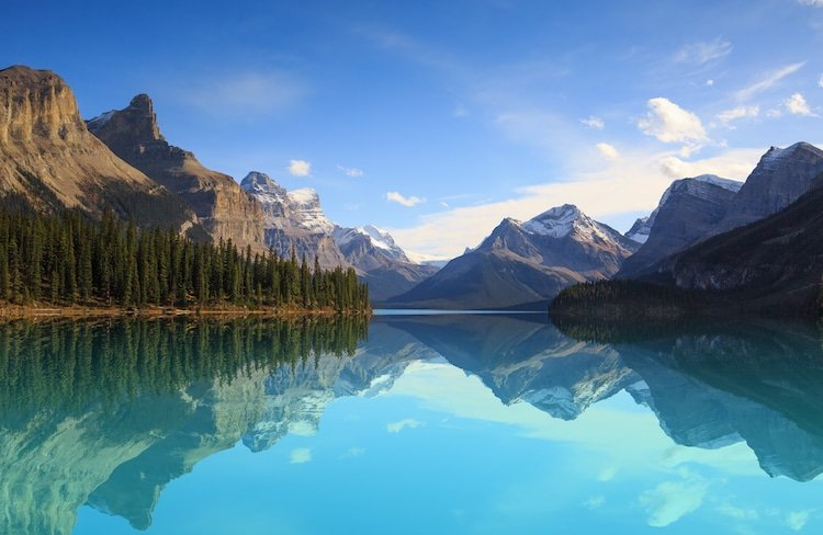 A glacial turquoise lake reflects the trees and mountains of Jasper National Park Alberta