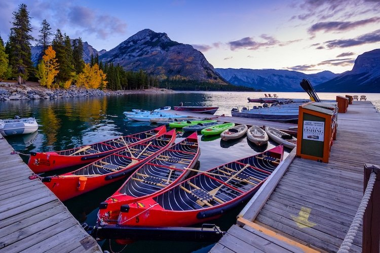 Beautiful autumn landscape scene in lake and mountain in background in west Canada, colour kayaks and canoes and small boats