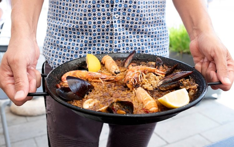 closeup of a young man holding a typical spanish seafood paella in the paellera, the paella pan