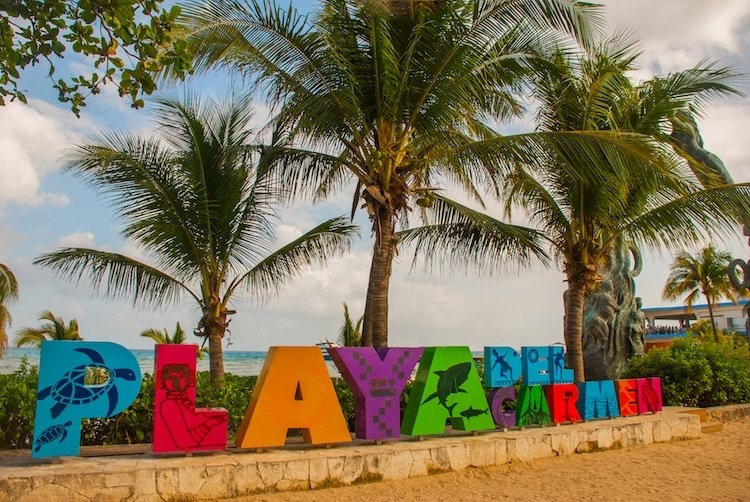 Playa del Carmen sign at Parque Fundadores surrounded by palm trees and sand