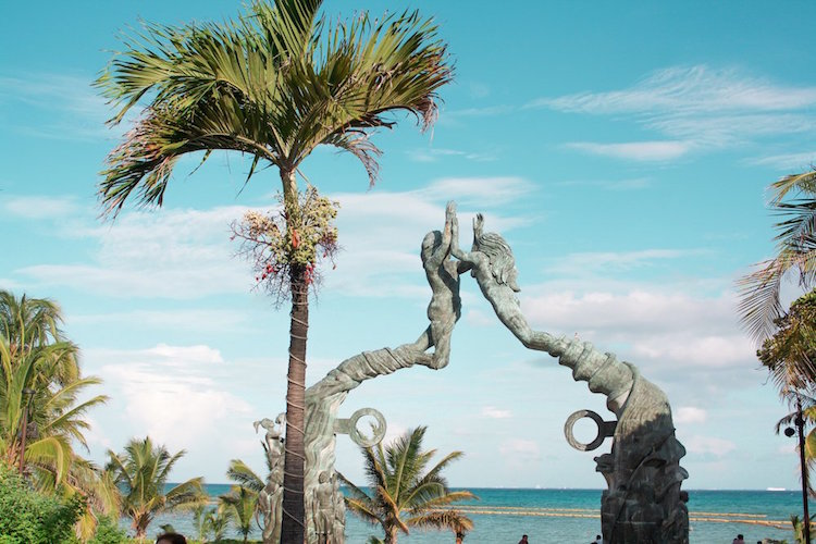 A Mayan sculpture is on display in front of the ocean in Playa del Carmen, Mexico.