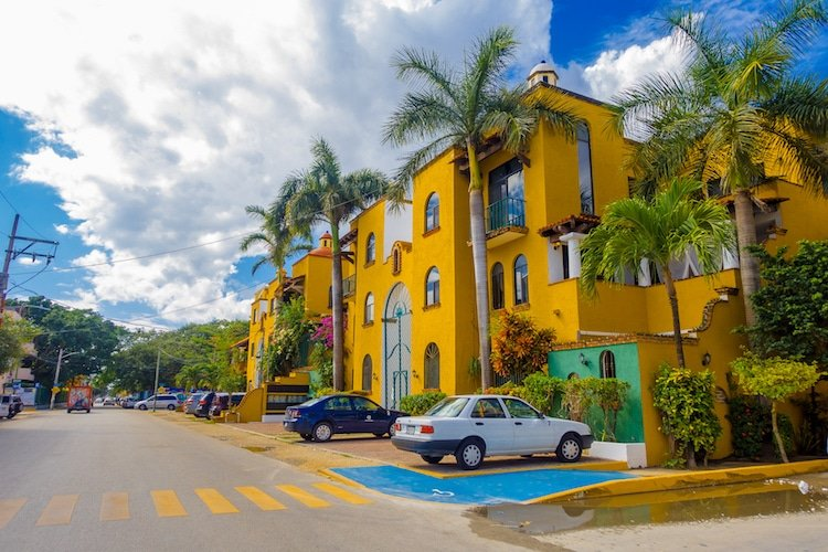 Bright yellow buildings with palm trees in Playa del Carmen