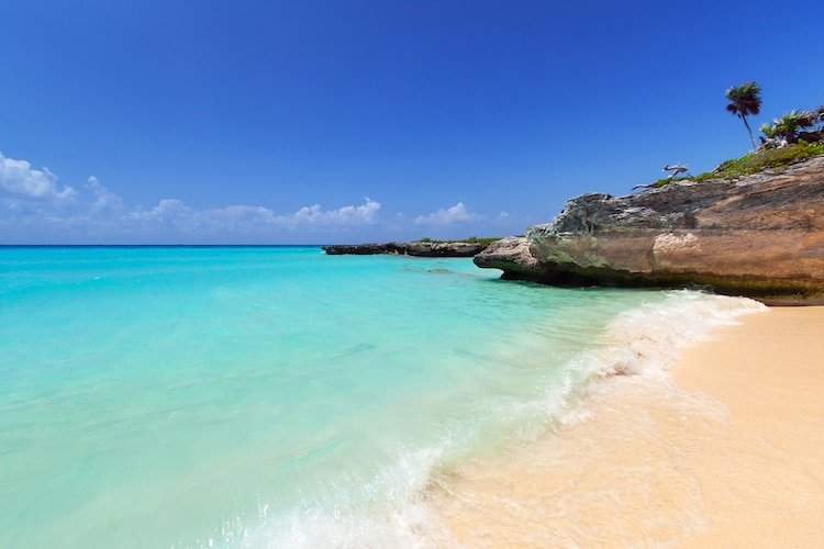 A tranquil photo of Punta Esmeralda, Playa del Carmen Mexico with clear waters and a rocky shoreline