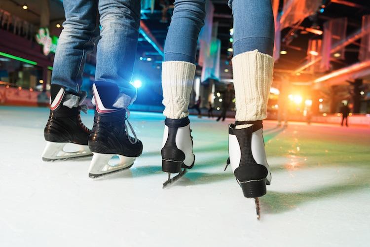Two people ice skate amongst city lights