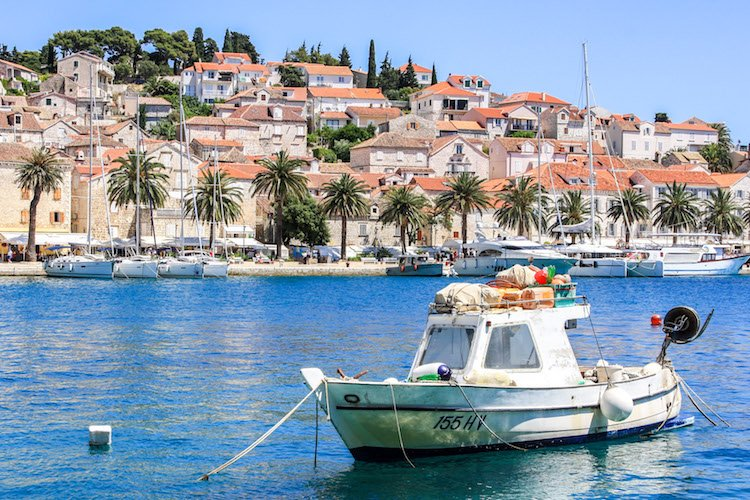 A boat is anchored in Hvar harbour, with terra-cotta roofed buildings in the background
