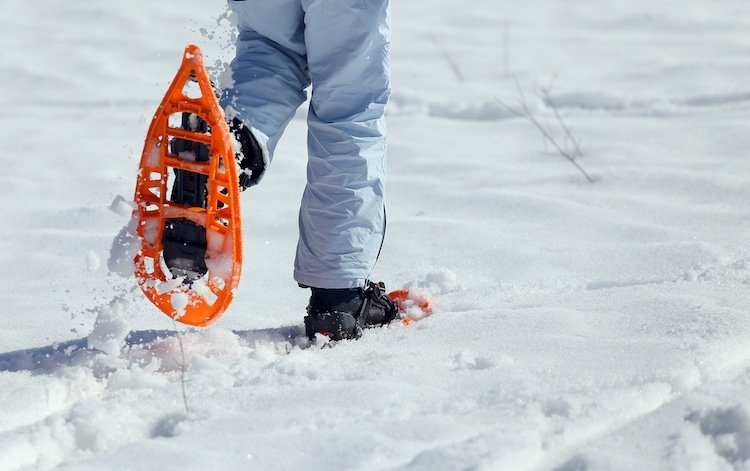 girl walking with two orange snowshoes