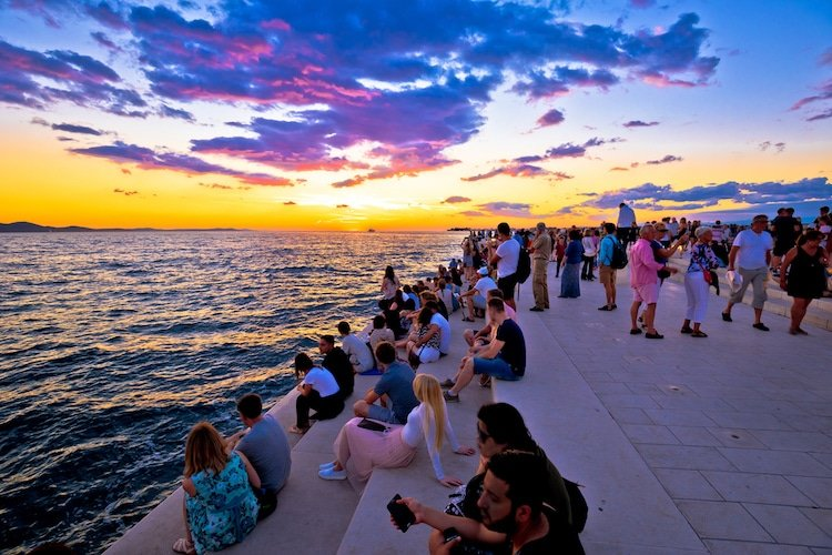 People line the boardwalk near the adriatic sea at sunset in Croatia