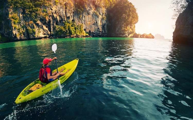 Young traveler paddling a kayak in a calm bay with limestone mountains