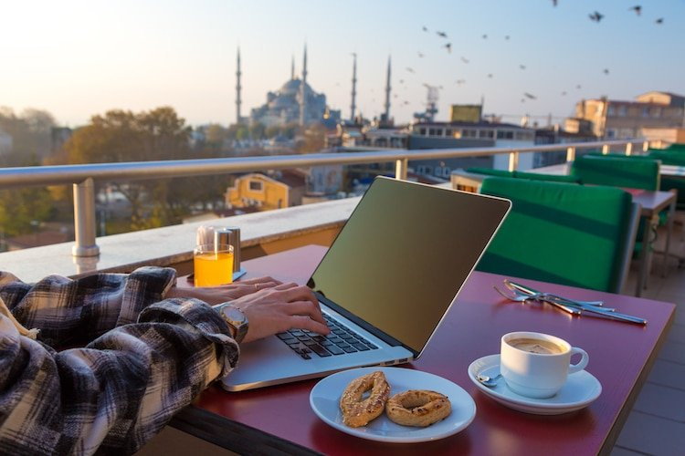 Person Working on Laptop Computer at Cafe Terrace on Table with Coffee Mug Orange Juice and Birds flying on background