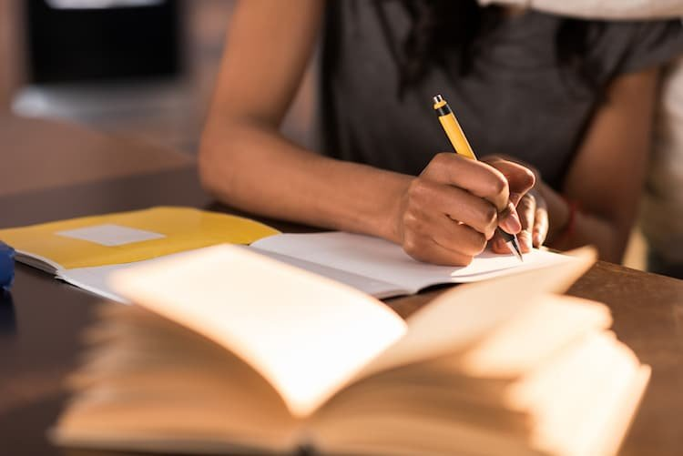 Person writing pen to paper on desk with other books nearby
