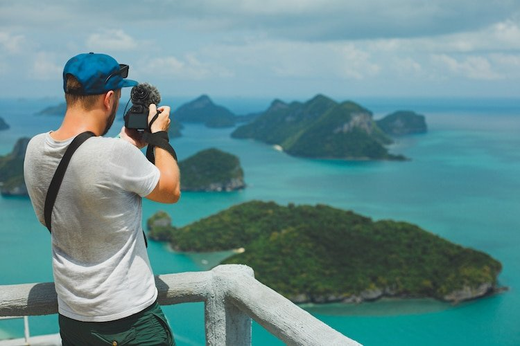 Man takes photo of lush islands with dslr camera