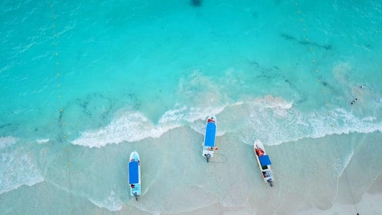 An aerial shot of three boats resting in the water of Tulum, Mexico