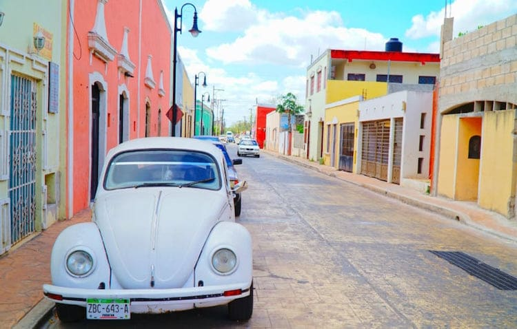 Valladolid Mexico - White VW bug in the foreground with colorful buildings lining the street.