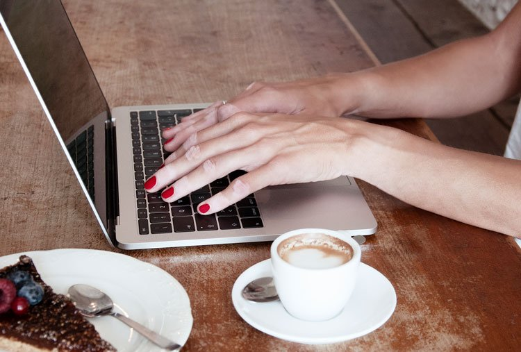 woman working on laptop with coffee in a cafe