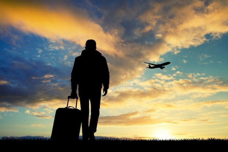 Man with a suitcase stands on the ground while an airplane flies nearby
