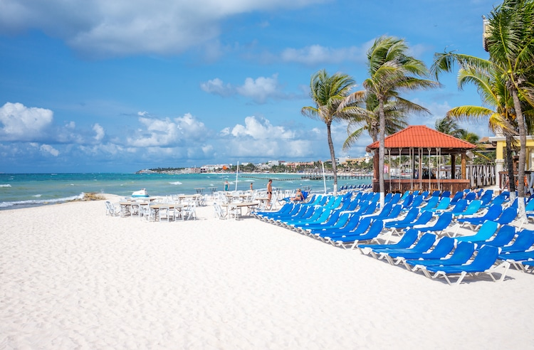 Blue lounge chairs line the beach in Playa del Carmen, Mexico
